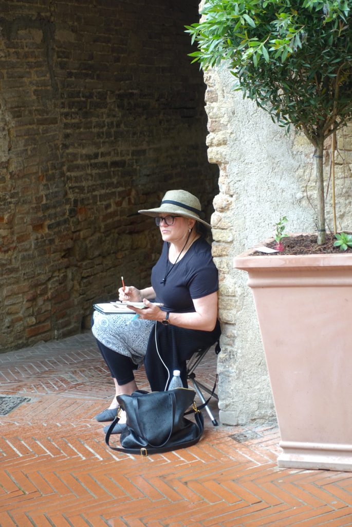 Plein air painters have to prepare for all weather conditions. In the rainy medieval village of San Gimignano, Julie finds shelter to work on her watercolor.
